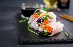 Vegetarian vietnamese spring rolls with spicy sauce, carrot, cucumber, red cabbage and rice noodle. Vegan food. Tasty meal.  Copy space