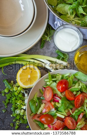 Vegetarianism and healthy food ,raw food. Cooking salad with vegetables, Kitchen table with dishes,plates and vegetables and herbs