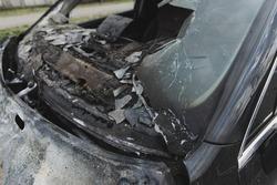 Vehicle after a crash accident. Black car after fire. Broken windshield. Closeup.