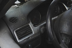 Vehicle after a crash accident. Car after fire. Car interior in ashes. Black dashboard and steering wheel closeup.
