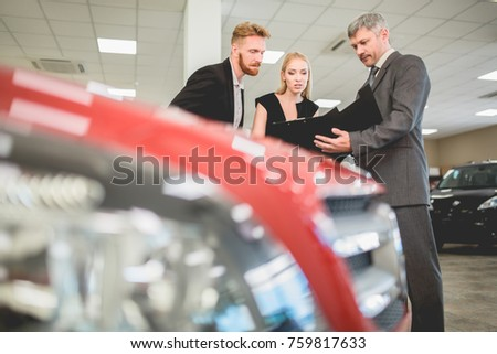 Vehicle dealer selling electro car to young couple. Man and woman talking with sales manager in auto showroom.