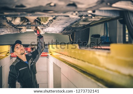 Vehicle Diagnostic Station. Caucasian Auto Service Worker Checking Car Under Carriage Looking For Potential Issues. #1273732141