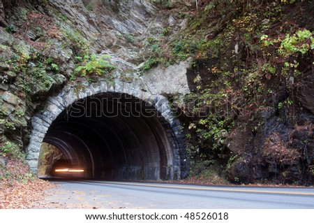 Vehicle drives through a tunnel through the mountains of Tennessee. Motion blur in car.