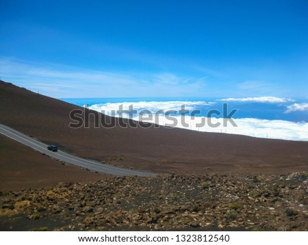 vehicle driving up a road at high altitude above the clouds on a road surrounded by volcanic ash and debris with blue sky background