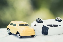 Vehicle insurance car accident concept : Two Miniature cars accidents crash on road, broken toys auto car on city map, green background.