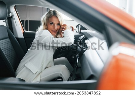 Vehicle interior. Woman in formal clothes is indoors in the autosalon.