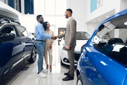 Vehicle Purchase. Happy Car Buyers Handshaking With Auto Seller Standing Among Luxury Automobiles In Dealership Showroom