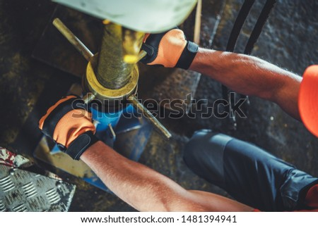Vehicle Repair Lift Support. Caucasian Mechanic Leveling and Securing Lifted Machine.