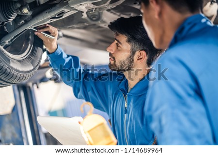Vehicle service maintenance handsome mens checking under car condition in garage. Automotive mechanic pointing flash light on wheel following maintenance checklist document. Car repair service concept
