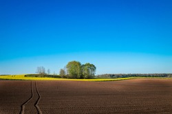 Vehicle tracks through a freshly ploughed agricultural field with rich brown fertile earth ready for planting the spring crop