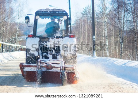 vehicle tractor clears and clears snow from the road with a snowy forest in sunny frosty weather