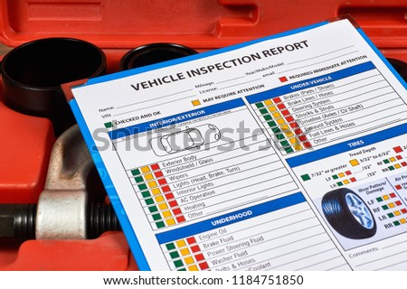 Vehicle vehicle inspection report form against the background of automotive tools. Close up.