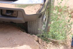 Vehicle wheel stuck in a dry ditch with bushes