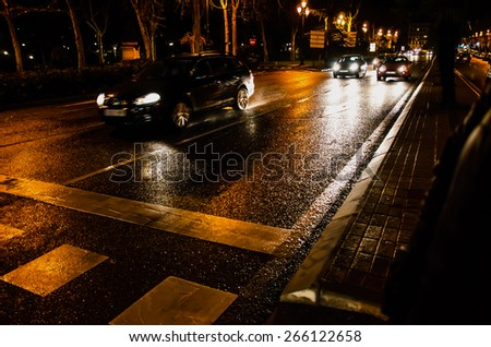 Vehicles in motion at night after rain. Night city lights
