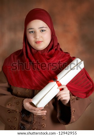 Veiled Moroccan student showing her diploma with red ribbon