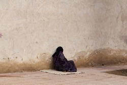 Veiled poor old woman dressed in traditional clothes sitting alone by a wall Morocco