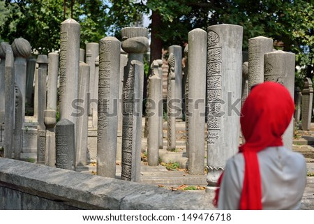 veiled woman praying in front of the old tombstones