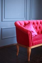 Velvet pink sofa and pink satin pillow. Blue wall