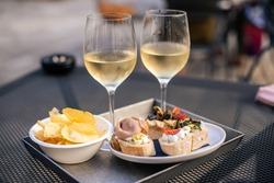 Venetian Cicchetti snacks and two glasses of white wine in a snack bar in Venice, Italy