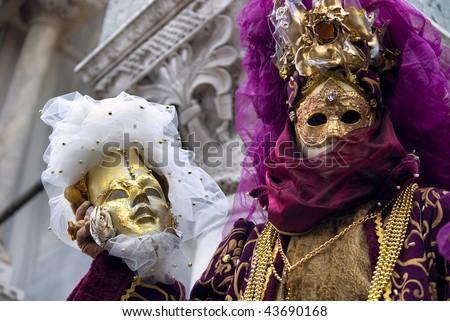 venetian figure in a fancy costume showing a carnival mask