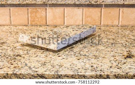Venetian Gold Granite:   Rough ashlar of Venetian Gold granite on a Venetian Gold granite counter. #758112292