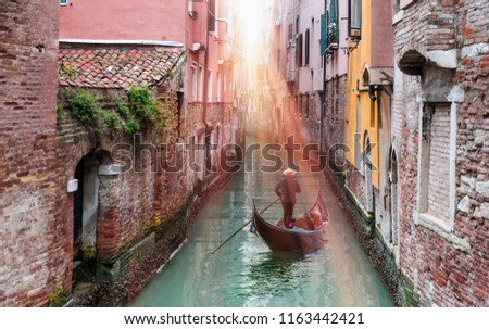 Venetian gondolier punting gondola through green canal waters of Venice Italy #1163442421