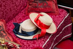 Venetian gondolier's red and blue hats on the sitting bench of a gondola, Venice, Italy