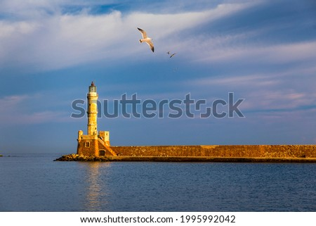 Venetian harbour and lighthouse in old harbour of Chania with seagulls flying over, Crete, Greece. Old venetian lighthouse in Chania, Greece. Lighthouse of the old Venetian port in Chania, Greece.