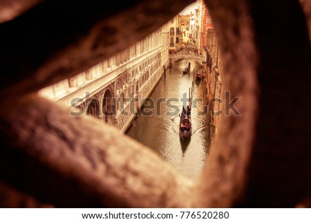 Venetian view from famous Bridge of Sighs in Venice, Italy. Bridge of Sighs (Ponte dei Sospiri) is the way from palace to prison in Venice in the past. Vintage photo of historical landmark of Venice.