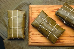 Venezuelan Christmas gastronomy, Hallacas on a wooden board and a background of banana leaves
