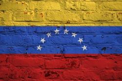 Venezuelan flag on brick wall background.