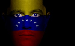 Venezuelan flag painted/projected onto a man's face.