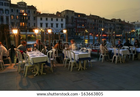 VENICE - APRIL 14: People in restaurant at evening. Outdoor restaurants located along Grand Canal close to famous Rialto Bridge are very popular with tourists visiting Venice, Italy on April 14, 2005.