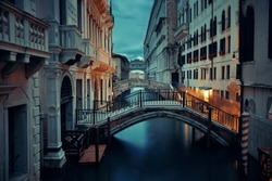 Venice canal view at night with bridge and historical buildings. Italy.
