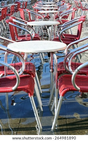 Venice, chairs and tables of the bar with water at high tide