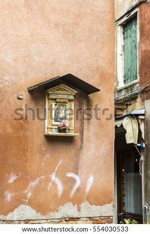 Venice, Italy - 08 April 2016: Painted icon image of a Saint or Ex-voto on a venetian orange wall, Venice, Italy #554030533