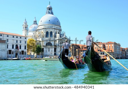 Venice, Italy - August 27, 2016: Gondoliers sail on gondolas full of tourists near Basilica Santa Maria della Salute #484940341