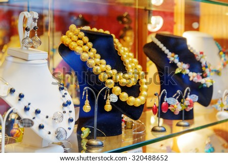 VENICE, ITALY - AUGUST 24, 2014: Original jewelry from Murano Glass in shop window on the Rialto Bridge. Beautiful beads, necklaces and earrings. Venice is a popular tourist destination of Europe.