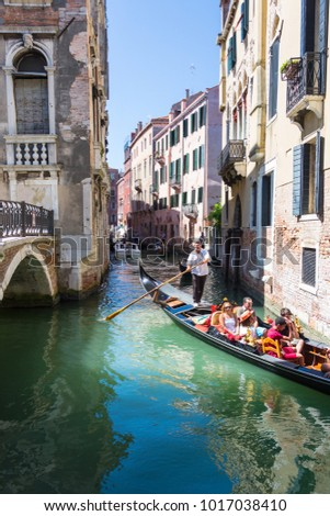 VENICE, ITALY - AUGUST 7 2016: Tourists are sailing on gondola Venice, Italy #1017038410
