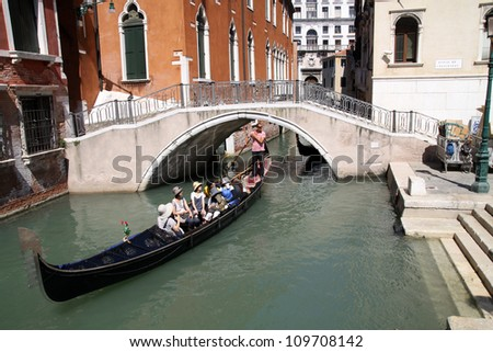 VENICE, ITALY - AUGUST 2: Tourists on a Gondola, August 2, 2012 in Venice, Italy. The city has an average of 50,000 tourists a day and it's one of the world's most internationally visited city