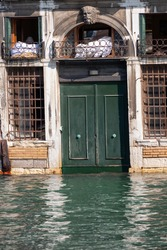 Venice, Italy. Close up of a waterfront building with wooden portal or door partly submerged by the water. Water at very high level submerging steps and doorways and almost touching the windows.