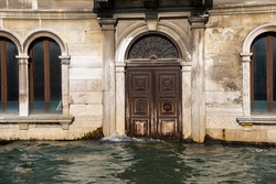 Venice, Italy. Close up of a waterfront bulding with wooden portal or door partlu submerged by the water. Water at very high level submerging steps and doorways and almost touching the windows.
