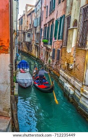 Venice, Italy - December 09, 2013: Gondolier in a small canal in Venice #712235449