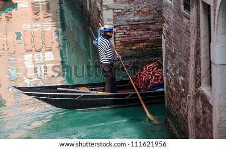 VENICE,ITALY-FEB 18:Unidentified gondolier entering a narrow canal in Venice on February 18,2012. There were several thousand gondolas in the 18th century, with only several hundred today for tourism.