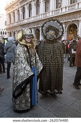 VENICE, ITALY - FEBRUARY 8, 2015: Two unidentified masked persons in costume on San Marco Square during the Carnival in Venice, Italy.