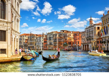 Venice, Italy. Gondolas with tourists floating by Grand Canal among antique buildings and traditional italian Venetian architecture. Sunny day with blue sky and clouds.