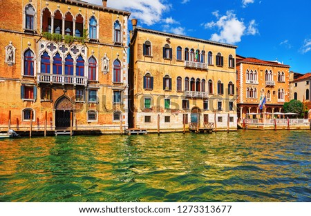 Venice, Italy. Grand Canal vintage street with old italian houses with piers. Summer day blue sky clouds. Decorative windows and walls.
