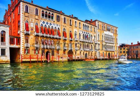 Venice, Italy. High-speed water motorboat floating by at Grand Canal vintage street among old italian houses with boats and by piers. Summer day blue sky clouds.