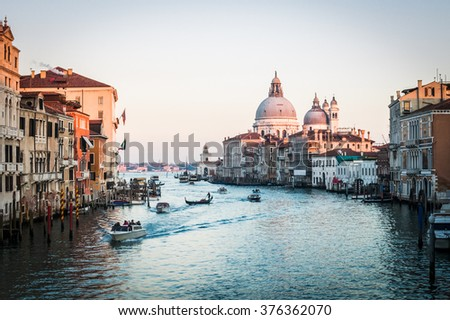 Venice, Italy - 20 January 2016:  Colour image at dusk showing boats moving along the Grand Canal with the iconic Santa Maria della Salute in the distance. #376362070