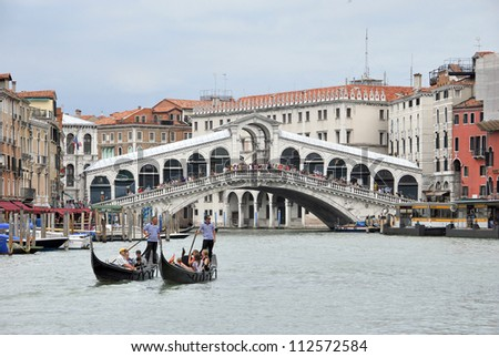 VENICE, ITALY - JULY 21:  Gondoliers standing on their gondolas near Rialto bridge on July 21, 2012 in Venice. Gondolas are passenger transportation boats typical for Venice, Italy